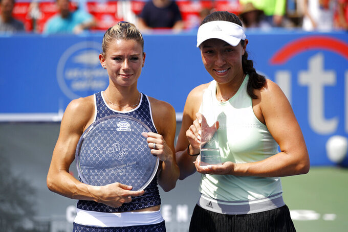 Runner-up Camila Giorgi, left, of Italy, and winner Jessica Pegula pose for photographs after a final match at the Citi Open tennis tournament, Sunday, Aug. 4, 2019, in Washington. (AP Photo/Patrick Semansky)