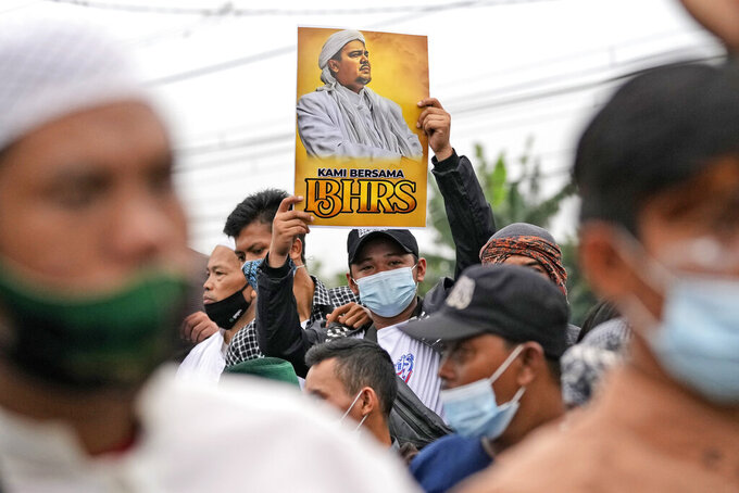 """A supporter holds up a poster bearing a portrait of firebrand cleric Rizieq Shihab during a rally near the district court where his sentencing hearing is held in Jakarta, Indonesia, Thursday, June 24, 2021. The influential cleric was sentenced to another four years in prison on Thursday for concealing information about his coronavirus test result. Writings on the poster read """"We are with Grand Imam Rizieq Shihab.""""(AP Photo/Dita Alangkara)"""