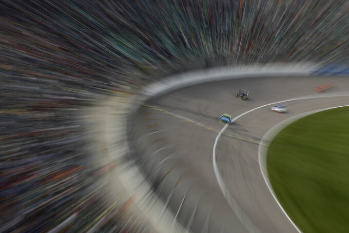 In this photo taken with a slow shutter, drivers race during a NASCAR Cup Series auto race at Kansas Speedway in Kansas City, Kan. Sunday, Oct. 20, 2019. Elliott placed second. (AP Photo/Charlie Riedel)