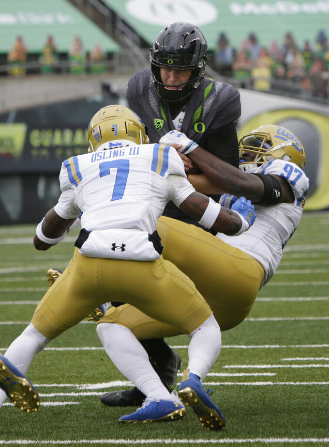 UCLA defensive players Mo Osling III, left, and Odua Isibor, right, sack Oregon quarterback Tyler Shough during the third quarter of an NCAA college football game Saturday, Nov. 21, 2020, in Eugene, Ore. (AP Photo/Chris Pietsch)