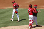 Los Angeles Angels starting pitcher Julio Teheran, left, walks away from the mound after manager Joe Maddon, right, pulls him the second inning of a baseball game against the Texas Rangers in Anaheim, Calif., Sunday, Sept. 20, 2020. Catcher Anthony Bemboom is center.  (AP Photo/Alex Gallardo)
