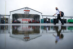 A man is reflected in a rain puddle as he walks near the Cup cars garages before the scheduled NASCAR Truck Series auto race at Pocono Raceway, Saturday, June 27, 2020, in Long Pond, Pa. (AP Photo/Matt Slocum)