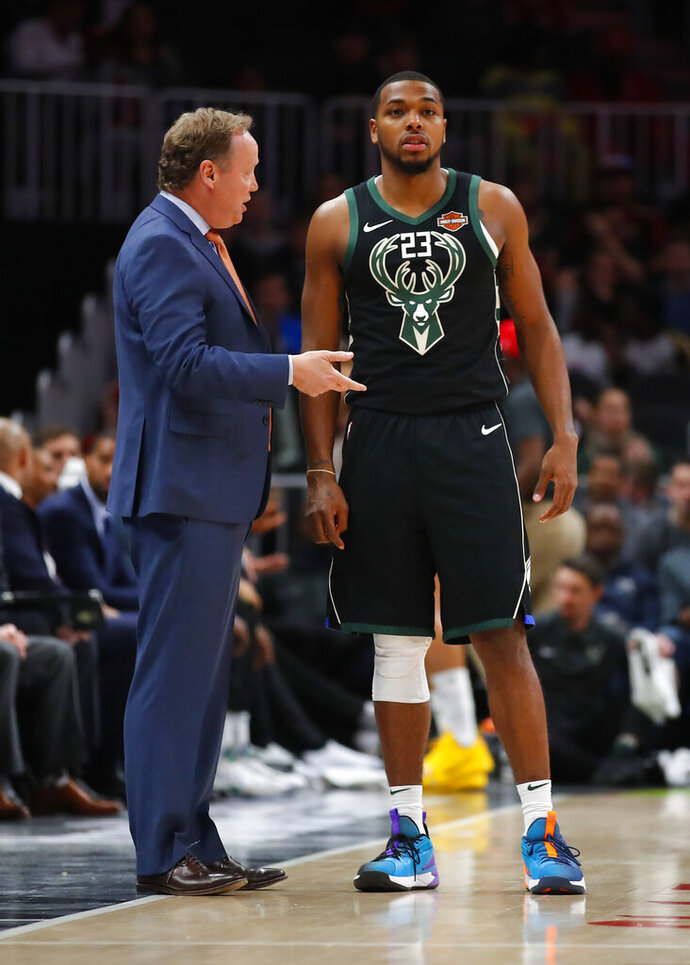 Milwaukee Bucks head coach Mike Budenholzer, left, speaks with guard Sterling Brown (23) in the first half of an NBA basketball game against the Atlanta Hawks on Sunday, March 31, 2019, in Atlanta. (AP Photo/Todd Kirkland)