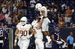 Texas' Roschon Johnson is lifted by offensive lineman Derek Kerstetter, center, after scoring against Rice during the first half of an NCAA college football game Saturday, Sept. 14, 2019, in Houston. (AP Photo/Eric Gay)