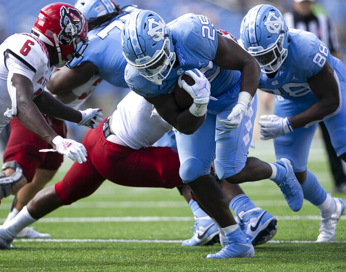 North Carolina's Javonte Williams (25) rushes for a first down against N.C. State in the first half of an NCAA college football game on Saturday, Oct. 24, 2020 in Chapel Hill, N.C. (Robert Willett/The News & Observer via AP)