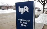 In this  Feb. 12, 2020, photograph, a sign for the car sharing service Lyft stands near a pickup zone outside the Pepsi Center in downtown Denver.  Just as the coronavirus outbreak has boxed in society, it's also squeezed high-flying tech companies reliant on people's freedom to move around and get together.  Lyft and rival Uber are turning to deliveries to make up for lost income after ride-hailing screeched to a halt. (AP Photo/David Zalubowski, File)