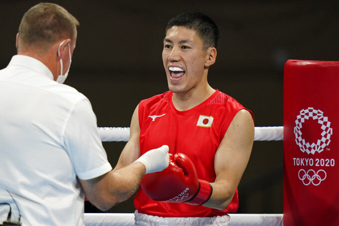 Japan's Daisuke Narimatsu is checked by the referee before the start of his men's lightweight 63-kg boxing match with Fiston Mbaya Mulumba, of the Democratic Republic of the Congo, at the 2020 Summer Olympics, Sunday, July 25, 2021, in Tokyo, Japan. (AP Photo/Frank Franklin II)