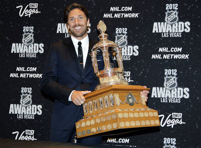 FILE - In this June 20, 2012, file photo, New York Rangers' Henrik Lundqvist poses with the Vezina Trophy after winning the award for the league's best goalie during the NHL Awards in Las Vegas. The New York Rangers have bought out the contract of star goaltender Henrik Lundqvist. The Rangers parted with one of the greatest netminders in franchise history on Wednesday, Sept. 30, 2020, when they paid off the final year of his contract.(AP Photo/Julie Jacobson, File)
