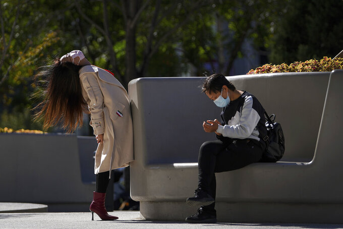 A woman wearing a face mask to help curb the spread of the coronavirus stretches her body next to a masked woman sitting on a bench outside a shopping mall in Beijing, Thursday, Oct. 21, 2021. (AP Photo/Andy Wong)