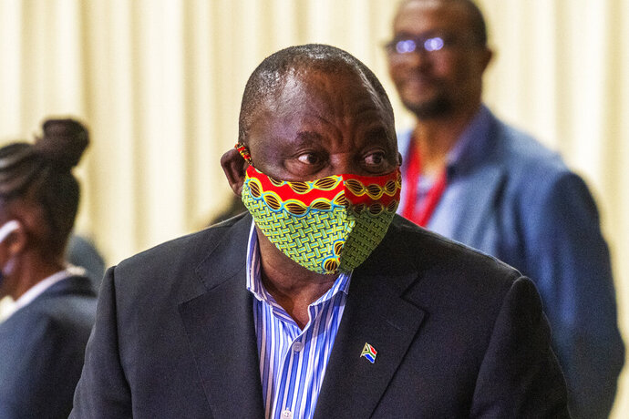 FILE — In this Friday, April 24, 2020 file photo, South African President Cyril Ramaphosa visits a field hospital in Johannesburg. Ramaphosa has announced he has gone into quarantine after coming into contact with a dinner guest who has tested positive for COVID-19. He came into contact with a guest at a dinner of 35 people in Johannesburg last weekend, the president's spokesman said Wednesday, Oct. 28. (AP Photo/Jerome Delay, File)