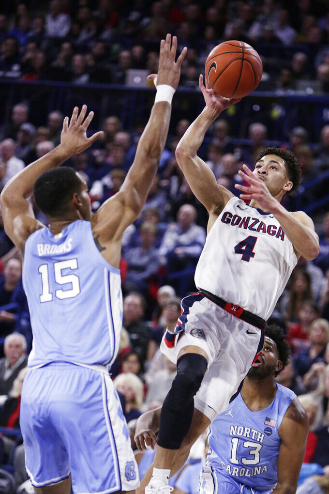 Gonzaga guard Ryan Woolridge (4) shoots over North Carolina forward Garrison Brooks (15) during the first half of an NCAA college basketball game in Spokane, Wash., Wednesday, Dec. 18, 2019. (AP Photo/Young Kwak)