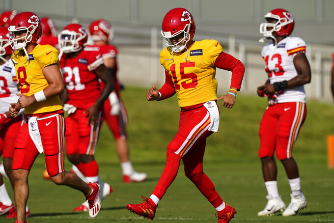 Kansas City Chiefs quarterback Patrick Mahomes (15) runs with teammates during an NFL football training camp Saturday, Aug. 15, 2020, in Kansas City, Mo. (AP Photo/Charlie Riedel)