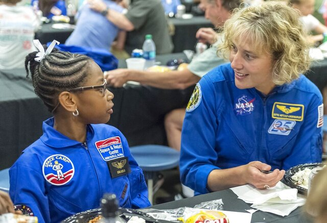 FILE - NASA astronaut Dottie Metcalf-Lindenburger talks with Space Camp camper Bria Jackson, of Atlanta, before giving a speech at the U.S. Space & Rocket Center in Huntsville, Ala. in this July 13, 2018 file photo. Space Camp, an educational program attended by nearly 1 million people, said Tuesday, July 28, 2020 it's in danger of closing without a cash infusion because of the coronavirus pandemic. (AP Photo/Vasha Hunt, File)
