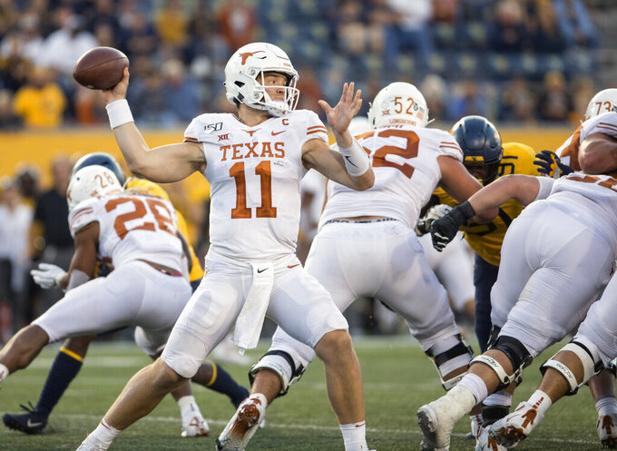 Texas quarterback Sam Ehlinger (11) attempts a pass during the second half of an NCAA college football game against West Virginia, Saturday, Oct. 5, 2019, in Morgantown, W.Va. (AP Photo/Raymond Thompson)