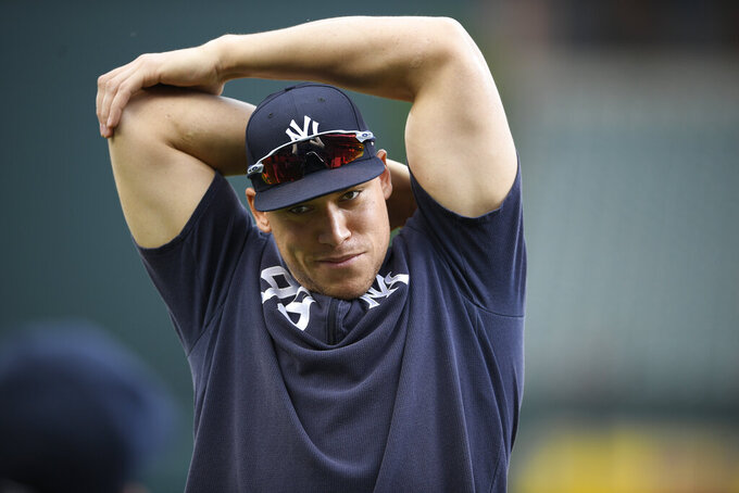 FILE - In this May 20, 2019, file photo, New York Yankees' Aaron Judge stretches on the field before a baseball game against the Baltimore Orioles, in Baltimore. Yankees general manager Brian Cashman is optimistic Aaron Judge, James Paxton, Aaron Hicks and Giancarlo Stanton will be ready to play in time for New York's rescheduled opener at World Series champion Washington on July 23. (AP Photo/Nick Wass, File)
