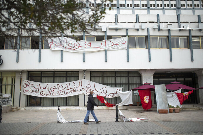 A man walks past an empty sit-in due to a national lockdown in Tunis' landmark Avenue Habib Bourgiba, where massive protests took place in 2011, on the tenth anniversary of the uprising , in Tunis, Thursday, Jan. 14, 2021. Tunisia is commemorating the 10th anniversary since the flight into exile of its iron-fisted leader, Zine El Abidine Ben Ali, pushed from power in a popular revolt that foreshadowed the so-called Arab Spring. But there will be no festive celebrations Thursday marking the revolution in this North African nation, ordered into lockdown to contain the coronavirus. (AP Photo/Mosa'ab Elshamy)