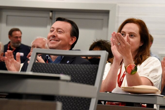 South Carolina Republican Party Chairman Drew McKissick, left, and his wife Amy, right, applaud during remarks by Gov. Henry McMaster during the Richland County GOP convention on Friday, April 30, 2021, in Columbia, S.C. (AP Photo/Meg Kinnard)