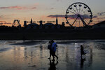 Visitors walk near the Palace Playland amusement park Wednesday, Aug. 5, 2020, at Old Orchard Beach, Maine. Tourists have returned to the popular seaside town in a state that ranks one of the lowest in the nation in positive cases of coronavirus. (AP Photo/Robert F. Bukaty)