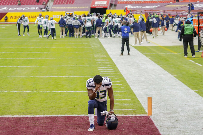 Seattle Seahawks wide receiver David Moore (83) kneels in the end zone before the start of an NFL football game against the Washington Football Team, Sunday, Dec. 20, 2020, in Landover, Md. Seattle went on to win 20-15. (AP Photo/Andrew Harnik)