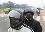 Commuters wear pollution masks and drive on a road on a smoggy afternoon in New Delhi, India, Thursday, Nov. 7, 2019. The air quality index stood at 273 on Thursday after authorities declared a health emergency last weekend when the index crossed 500 — 10 times the level considered healthy by WHO standards. (AP Photo/Manish Swarup)