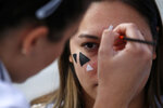In this photo taken Sept. 25, 2019, members of a rights group paint a face with makeup to confuse the Huawei surveillance video cameras with face-recognition software in Belgrade, Serbia. With public authorities disclosing little about how the cameras work, the group has set up a tent to ask pedestrians whether they know they are being watched.  (AP Photo/Darko Vojinovic)