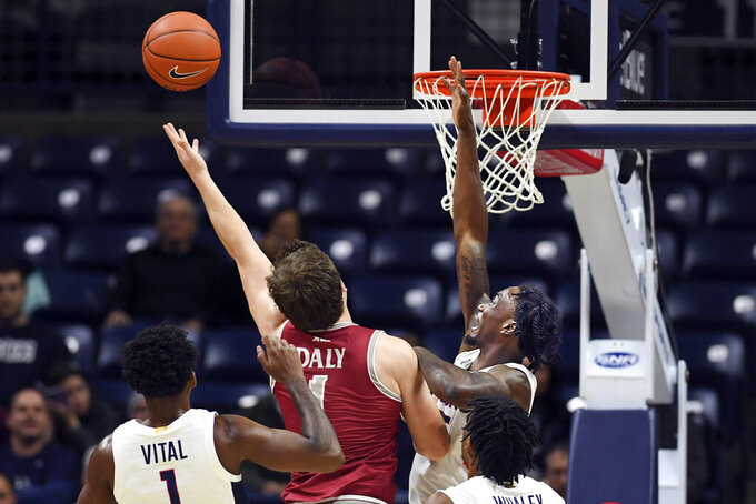 Saint Joseph's guard Ryan Daly (1) scores over Connecticut's Sidney Wilson (15) in the first half of an NCAA college basketball game Wednesday, Nov. 13, 2019, in Storrs, Conn. (AP Photo/Stephen Dunn)