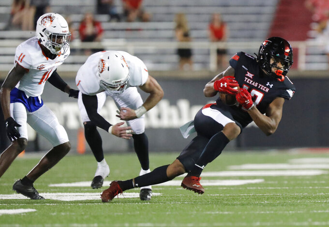 Texas Tech's Erik Ezukanma gets away from Houston Baptist's Devion Hargrove and (11) and Patrick Wolfe (1) during the second half of an NCAA college football game, Saturday, Sept. 12, 2020, in Lubbock, Texas. (AP Photo/Mark Rogers)