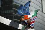 Two anti-Brexit people hold EU, Ireland and Union Flags stand outside the European Commission in Brussels, Friday, Oct. 11, 2019. EU negotiator Michel Barnier says that he had a