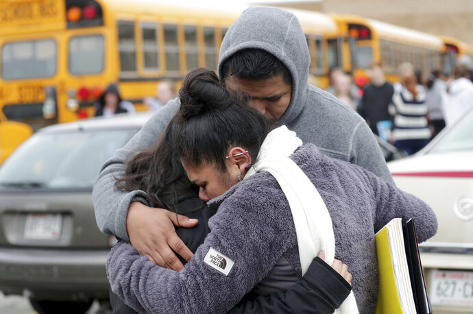 FILE - In this Dec. 2, 2019 file photo, Becky Galvan, center, consoles her daughter, Ashley Galvan, a 15-year-old sophomore, with her father Jose Chavez outside Waukesha South High School in Waukesha, Wis., after gunshots were exchanged between a student and a school resource officer inside the school.  The involvement of school resource officers in two separate student shootings this week in Wisconsin highlights the role they can play in a worst-case scenario. While the thousands of officers in schools are dedicated to law enforcement first, they spend much of their days as counselors and educators. In cases of real and immediate threats to students or teachers, however, the rules on use of force are set by the police departments that assign them to the schools. (Mike De Sisti/Milwaukee Journal-Sentinel via AP, File)