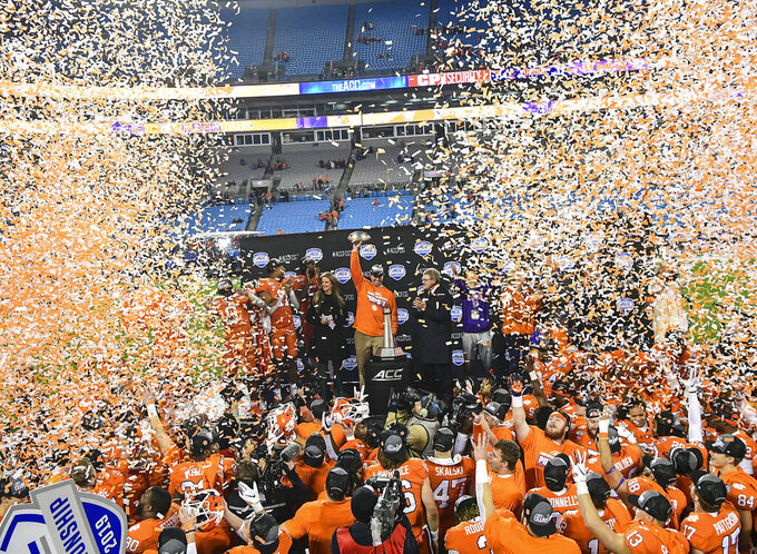 Clemson coach Dabo Swinney raises the Atlantic Coast Conference championship trophy after the team's win over Virginia in an NCAA college football game in Charlotte, N.C., Saturday, Dec. 7, 2019. (Ken Ruinard/The Independent-Mail via AP)
