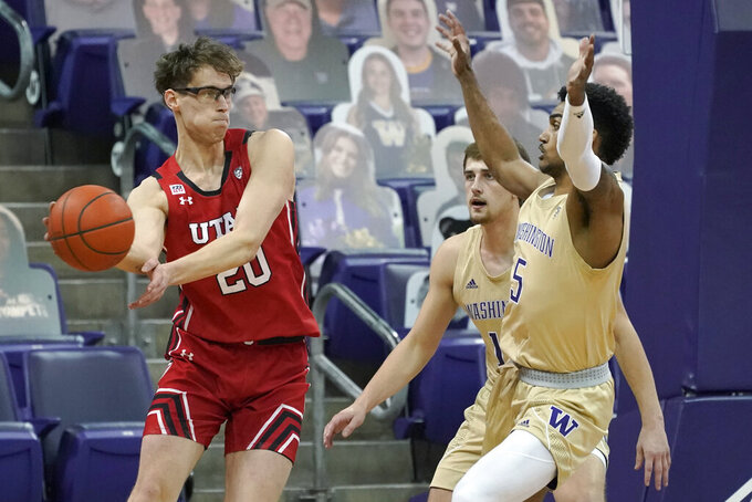 Utah forward Mikael Jantunen, left, passes around Washington guard Jamal Bey (5) during the first half of an NCAA college basketball game, Sunday, Jan. 24, 2021, in Seattle. (AP Photo/Ted S. Warren)