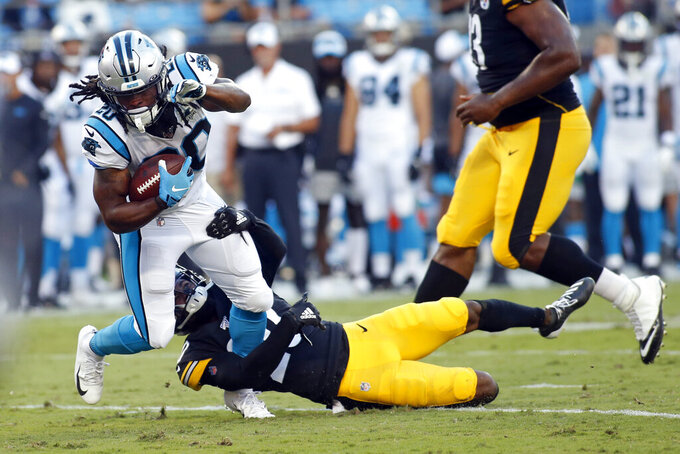Carolina Panthers running back Jordan Scarlett (20) runs while Pittsburgh Steelers cornerback Cameron Sutton (20) tackles during the first half of an NFL preseason football game in Charlotte, N.C., Thursday, Aug. 29, 2019. (AP Photo/Brian Blanco)