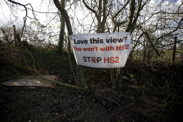 A protest sign is displayed by a roadside protest camp across the street from a High Speed 2 (HS2) rail line compound near the village of Harefield in north west London, Tuesday, Feb. 11, 2020. Britain's Conservative government is set to approve a contentious, expensive plan for a high-speed rail line linking London with central and northern England, despite opposition from environmentalists and even some members of the governing party. (AP Photo/Matt Dunham)