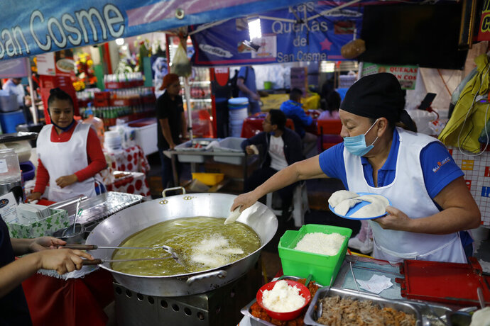 Sabina Hernandez Bautista, 59, prepares food in a stall inside Mercado San Cosme, where some vendors have put in place their own protective measures against coronavirus while others continue to work without masks or barriers, in Mexico City, Thursday, June 25, 2020.