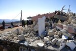 Firefighters stand next to a demolished Greek Orthodox church of Profitis Ilias after a strong earthquake in Arkalochori village on the southern island of Crete, Greece, Monday, Sept. 27, 2021. A strong earthquake with a preliminary magnitude of 5.8 has struck the southern Greek island of Crete, and Greek authorities say one person has been killed and several more have been injured. (AP Photo/Harry Nikos)