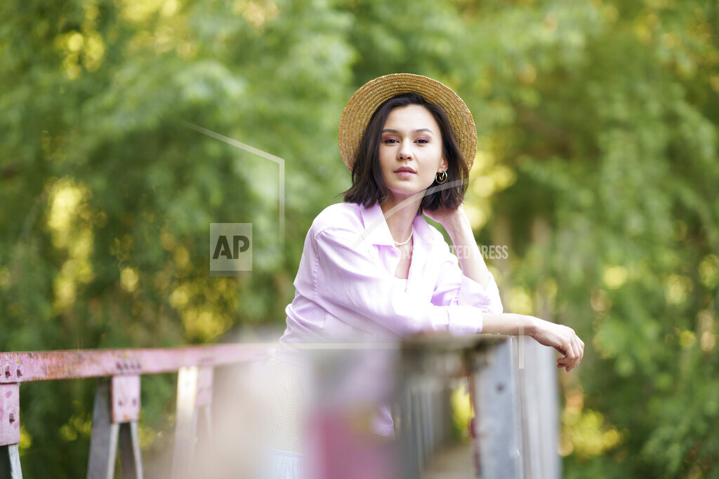 Beautiful young woman wearing hat standing on bridge in the countryside