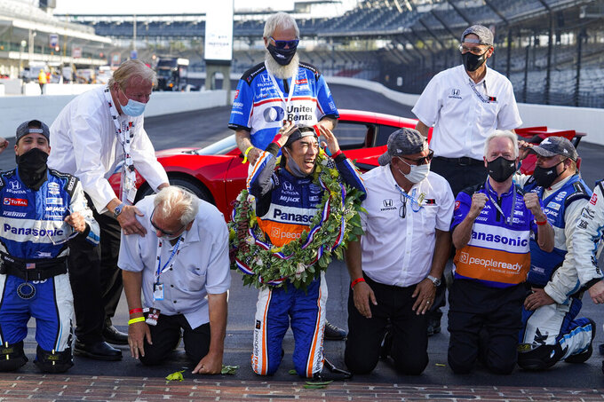 Takuma Sato, center, of Japan, kneels along the start-finish line after winning the Indianapolis 500 auto race at Indianapolis Motor Speedway in Indianapolis, Sunday, Aug. 23, 2020. (AP Photo/Michael Conroy)