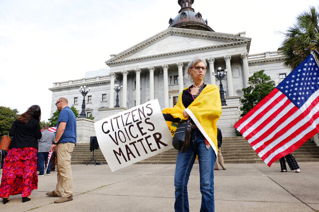 Kim Rulf, of Greenville, South Carolina, attends a protest on the South Carolina Statehouse grounds in Columbia, S.C., Tuesday, Sept. 15, 2020, calling for Gov. Henry McMaster to end the state of emergency issued for the coronavirus pandemic and for lawmakers to remove mask mandates across the state. About 50 people gathered without wearing masks at the Capitol building on the morning the state legislature was set to begin a two-week special session. (AP Photo/Michelle Liu)