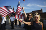 """FILE - In this undated file photo, Melissa Moore, right, a Republican who is running for a seat in the Minnesota Legislature, waves an American flag with members of VFW 7051 in the background in St. Louis Park, Minn. Moore is among about two dozen legislative candidates in at least a dozen states who have shown varying levels of engagement with the QAnon conspiracy theory. """"I like following it,"""" Moore said. """"It's an exciting movement that opens up our minds to different possibilities of what's going on, of what's really happening in our world today."""" (Richard Tsong-Taatarii/Star Tribune via AP, File)"""