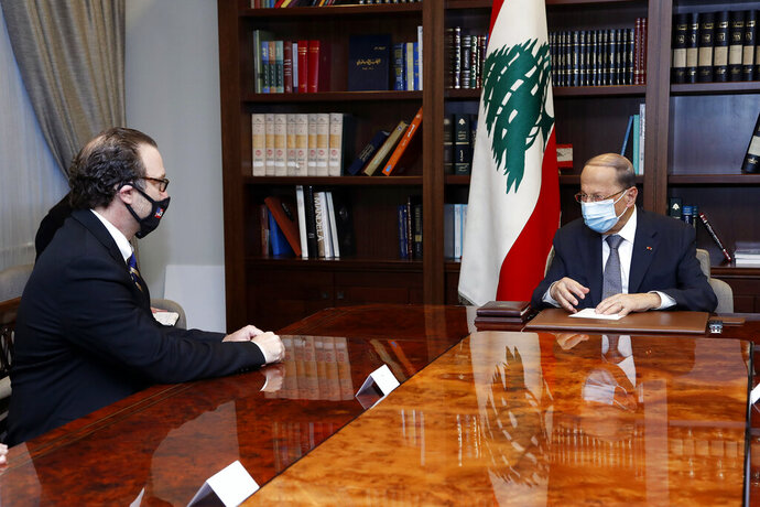 In this photo released by Lebanon's official government photographer Dalati Nohra, Lebanese President Michel Aoun, right, meets with U.S. Assistant Secretary of State for Near Eastern Affairs David Schenker at the Presidential Palace in Baabda, east of Beirut, Lebanon, Friday, Oct. 16, 2020. (Dalati Nohra/Lebanese Government via AP)