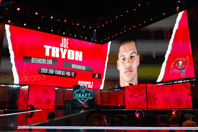An image of Washington defensive lineman Joe Tryon is displayed on stage after he was chosen by the Tampa Bay Buccaneers with the final pick in the first round of the NFL football draft, early Friday, April 30, 2021, in Cleveland. (AP Photo/Tony Dejak)