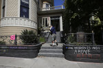 James Juanillo waves to people as he walks to his home in San Francisco, Sunday, June 14, 2020. The CEO of a cosmetic company issued an apology Sunday after she and her husband confronted Juanillo and threatened to call police because he stenciled