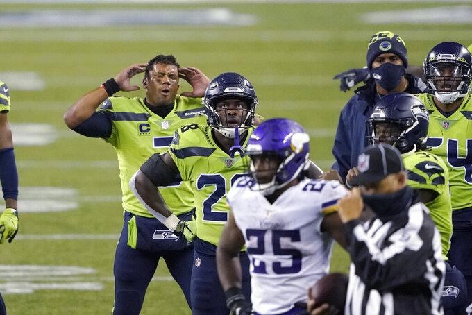 Seattle Seahawks quarterback Russell Wilson, left, and teammates wait with Minnesota Vikings players on the field for a final review of a play at the end of the second half of an NFL football game, Sunday, Oct. 11, 2020, in Seattle. The call went in the Seahawks' favor and they won 27-26. (AP Photo/Ted S. Warren)