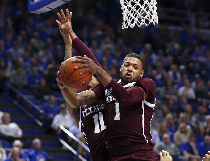 Texas A&M's Savion Flagg (1) pulls down a rebound next to teammate Wendell Mitchell (11) during the first half of an NCAA college basketball game in Lexington, Ky., Tuesday, Jan. 8, 2019. (AP Photo/James Crisp)