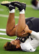 New Orleans Saints defensive end Payton Turner (98) stretches during during NFL football practice in Arlington, Texas, Tuesday, Aug. 31, 2021. (AP Photo/LM Otero)