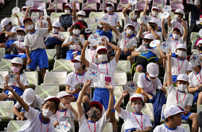 Students cheer prior to a men's soccer match between New Zealand and South Korea at the 2020 Summer Olympics, Thursday, July 22, 2021, in Kashima, Japan. (AP Photo/Fernando Vergara)