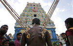 FILE - In this July 16, 2019 file photo, a Sri Lankan Hindu devotee stands with his body pierced with metal hooks as part of performing a ritual at a temple in Colombo, Sri Lanka. The Indian Ocean island nation of Sri Lanka, which will elect a new president on Saturday, Nov. 16, 2019 has had a tumultuous history. Since gaining independence from British colonial rule in 1948, the country has seen three major armed conflicts in which hundreds of thousands have died. It also has had its share of natural disasters. As it prepares to elect its seventh president, Sri Lanka remains a divided nation, with ethnic, political and economic issues unresolved. (AP Photo/Eranga Jayawardena, File)