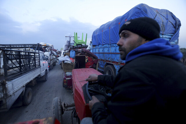 Civilians flee a Syrian military offensive in Idlib province on the main road near Hazano, Syria, Tuesday, Dec. 24, 2019. Syrian forces launched a wide ground offensive last week into the northwestern province of Idlib, which is dominated by al-Qaida-linked militants. The United Nations estimates that some 60,000 people have fled from the area, heading south, after the bombings intensified earlier this month. (AP Photo/Ghaith al-Sayed)