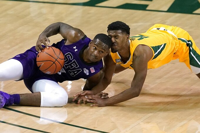 Stephen F. Austin guard Cameron Johnson, left, grabs a loose ball away from Baylor guard Jared Butler during the first half of an NCAA college basketball game in Waco, Texas, Wednesday, Dec. 9, 2020. (AP Photo/Tony Gutierrez)