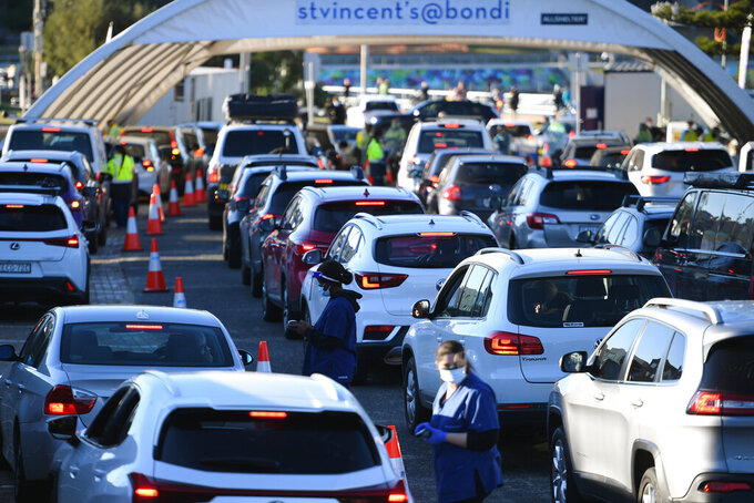 People queue in their cars to get tested for COVID-19 at a pop-up testing clinic at Bondi Beach in Sydney Friday, June 25, 2021. Parts of Sydney will go into lockdown late Friday after a coronavirus outbreak in Australia's largest city continued to grow. (Dean Lewins/AAP Image via AP)